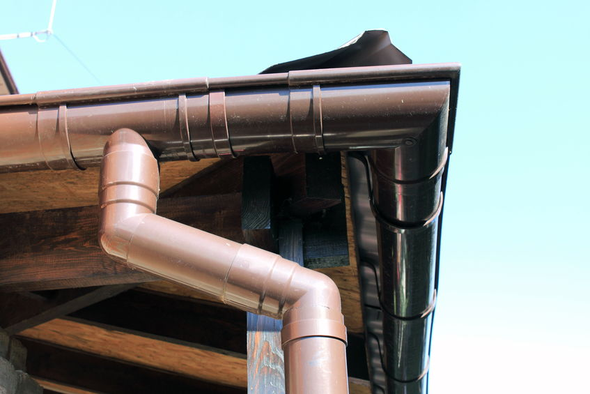 43764503 - brown rain gutter on a home against blue sky